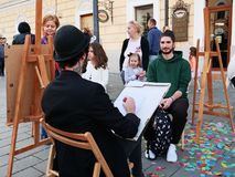 Young street artist draws pencil portrait live of people. Cluj-Napoca, Romania - May 20, 2018: Young male street artist draws pencil portrait live of people on stock photos