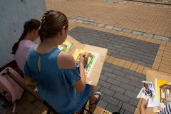 Young street artists learn to paint buildings stock photo