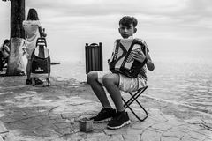 Young Street Musician Boy - Turkey. Young street musician boy playing his accordion while tourists enjoying their summer in Cinarcik Town. Cinarcik town is a royalty free stock photography