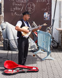 Young street musician playing the lute on the waterfront Royalty Free Stock Photo