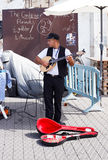 Young street musician playing the lute on the waterfront Royalty Free Stock Photos