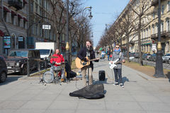 Young street musicians play on Bolshaya Konyushennaya Street in the sunny April afternoon. ST. PETERSBURG, RUSSIA - APRIL 10, 2017: Young street musicians play Royalty Free Stock Image