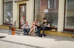 Young street musicians singing plays instruments. VILNIUS, LITHUANIA - MAY 18: three young street musicians singing and plays with instruments on the street on royalty free stock photo