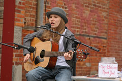 Young street performer. Young teen male performing with guitar at street fair Royalty Free Stock Photos