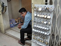 A young street vendor selling locks Royalty Free Stock Photos