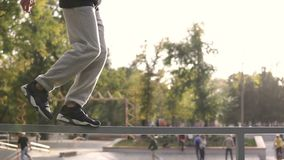 Young streetstyle man walk by railing on the border of skatepark in autumn city. stock video footage