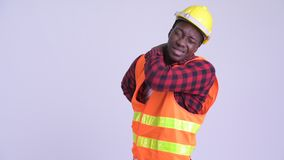 Young stressed African man construction worker having back pain