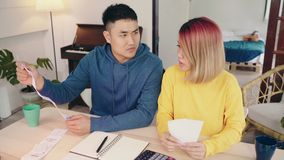Young stressed asian couple managing finances, reviewing their bank accounts using laptop computer and calculator at modern home. Woman and man doing paperwork stock video footage