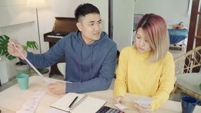 Young stressed asian couple managing finances, reviewing their bank accounts using laptop computer and calculator at modern home. Woman and man doing paperwork stock video