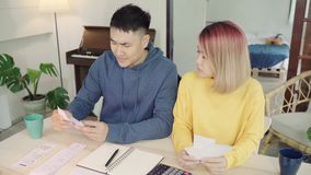 Young stressed asian couple managing finances, reviewing their bank accounts using laptop computer and calculator at modern home. Woman and man doing paperwork stock footage