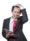 Young Stressed business man holding tablet and bite pen Stock Image