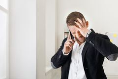 Young stressed businessman call mobile phone in modern office Royalty Free Stock Image