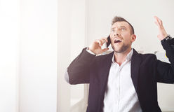 Young stressed businessman call mobile phone in modern office Royalty Free Stock Photos