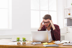 Young stressed businessman with laptop in modern white office Stock Image
