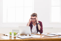 Young stressed businessman with laptop in modern white office Stock Images