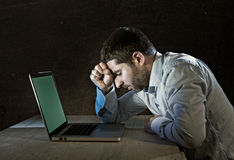 Young stressed businessman working on desk with computer laptop in frustration and depression. Young stressed businessman working with computer laptop thinking Royalty Free Stock Images