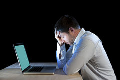 Young stressed businessman working on desk with computer laptop in frustration and depression Royalty Free Stock Image