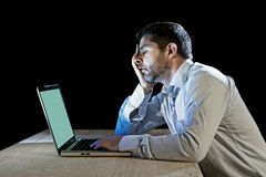 Young stressed businessman working on desk with computer laptop in frustration and depression Stock Photo