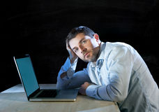 Young stressed businessman working on desk with computer laptop in frustration and depression. Young stressed businessman working with computer laptop in Royalty Free Stock Images