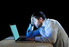 Young stressed businessman working on desk with computer laptop in frustration and depression. Young stressed businessman working with computer laptop in Stock Photo