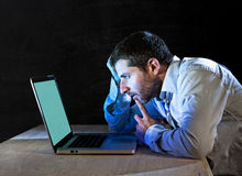 Young stressed businessman working late night on desk with computer laptop Stock Images