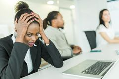 Young stressed businesswoman battling with a headache during a b Royalty Free Stock Images