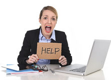 Young stressed businesswoman holding help sign overworked at office computer. Young attractive frustrated businesswoman holding help message overworked at office Royalty Free Stock Photography
