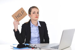 Young stressed businesswoman holding help sign overworked at office computer Royalty Free Stock Photo