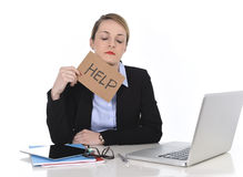 Young stressed businesswoman holding help sign overworked at office computer Royalty Free Stock Images