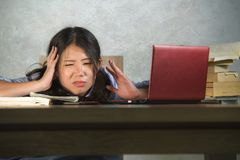 Young stressed and frustrated Asian Chinese student girl working hard with laptop computer and books pile on desk overwhelmed and. Exhausted feeling tired and stock photo