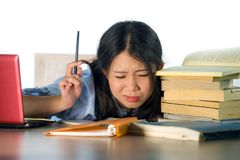 Young stressed and frustrated Asian Chinese teenager student working hard with laptop computer and books pile on desk overwhelmed. And exhausted feeling tired royalty free stock photo