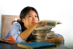 Young stressed and frustrated Asian Chinese teenager student working hard leaning on notepads and books pile on desk overwhelmed. And exhausted feeling tired royalty free stock photo