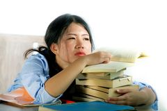 Young stressed and frustrated Asian Chinese teenager student working hard leaning on notepads and books pile on desk overwhelmed. And exhausted feeling tired royalty free stock photography