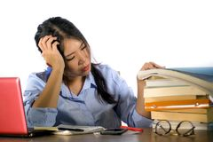 Young stressed and frustrated Asian Korean student girl working hard with laptop computer and books pile on desk overwhelmed and. Exhausted feeling tired and royalty free stock images