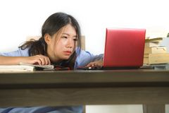 Young stressed and frustrated Asian Korean student girl working hard with laptop computer and books pile on desk overwhelmed and royalty free stock images