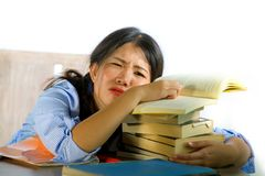 Young stressed and frustrated Asian Korean teenager student working hard leaning on notepads and books pile on desk overwhelmed. And exhausted feeling tired and royalty free stock images