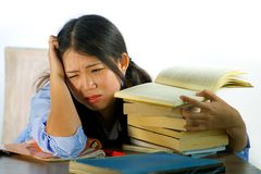 Young stressed and frustrated Asian Korean teenager student working hard leaning on notepads and books pile on desk overwhelmed stock image