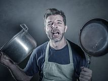 Young stressed and funny lazy man with apron holding kitchen pan and kitchen pot screaming in stress desperate crying isolated bac royalty free stock photos