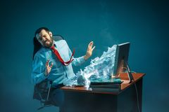 Young stressed handsome businessman working at desk in modern office shouting at laptop screen and being angry about. E-mail spam. Collage with a mountain of Royalty Free Stock Images