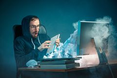 Young stressed handsome businessman working at desk in modern office shouting at laptop screen and being angry about. E-mail spam. Collage with a mountain of Royalty Free Stock Photography