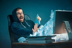 Young stressed handsome businessman working at desk in modern office shouting at laptop screen and being angry about. E-mail spam. Collage with a mountain of Stock Image