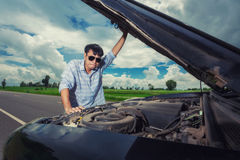 Young stressed man having trouble with his broken car looking in frustration on failed engine Stock Photos