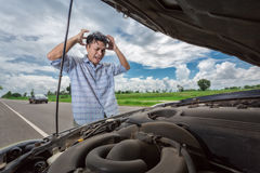 Young stressed man having trouble with his broken car looking in frustration on failed engine Royalty Free Stock Photo