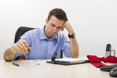 Young stressed manager analyzing some charts. With hand at his temple Stock Image