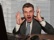 Young stressed and overwhelmed businessman in suit and necktie desperate working at office laptop computer desk screaming crazy royalty free stock photography