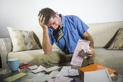 Young stressed and overwhelmed man biting calculator holding mess of bank and receipts paperwork desperate calculating monthly exp. Enses taxes and income royalty free stock photos