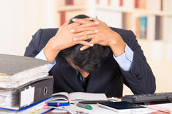 Young stressed overwhelmed man with piles of