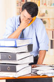 Young stressed overwhelmed man with piles of Royalty Free Stock Photos