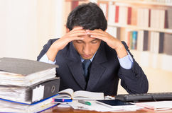 Young stressed overwhelmed man with piles of Stock Photo