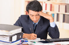 Young stressed overwhelmed man with piles of Royalty Free Stock Image